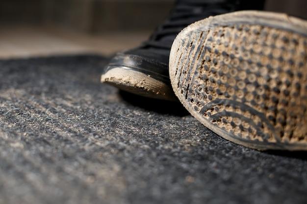 Vuile schoenen staan op een zwart tapijt met een verspreid moeras