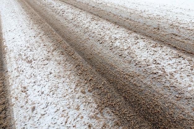 Vuile sneeuw, die sporen van transport op de weg afdrukte. foto die in de winter onder een hoek is genomen.