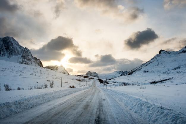 Vuile sneeuwweg met zonlicht op bergen