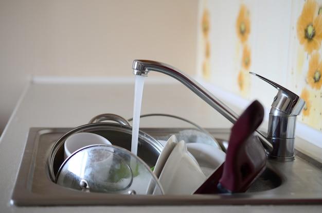 Vuile vaat en ongewassen keukentoestellen liggen in schuimwater onder een kraan van een keukenkraan
