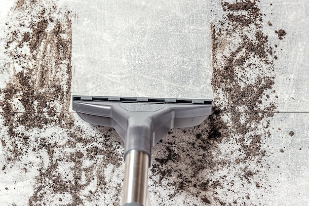 Vuile vloer schoonmaken met stofzuiger in de woonkamer, tapijtstofzuiger.