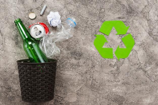 Vuilnisbak met afval naast recycling logo