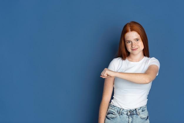 Vuist bult. het portret van het blanke jonge meisje op blauw. mooi vrouwelijk roodharig model met schattige sproeten.