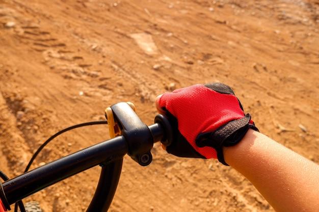 Vuist van een jongen met rode fietserhandschoenen die op een onverharde weg trappen.