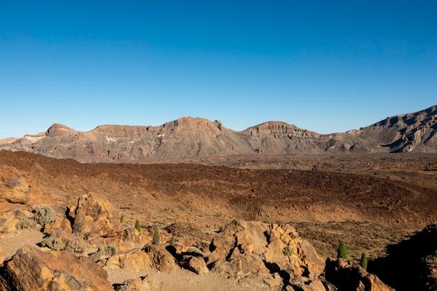 Vulkanische rode grondkrater met heldere hemel