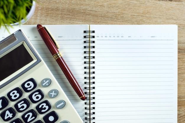 Vulpen of inkt pen met notebookpapier en rekenmachine op houten werktafel
