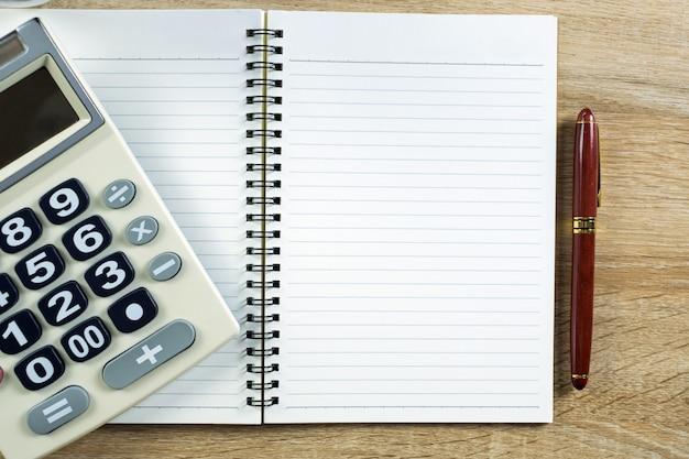 Vulpen of inkt pen met notebookpapier en rekenmachine