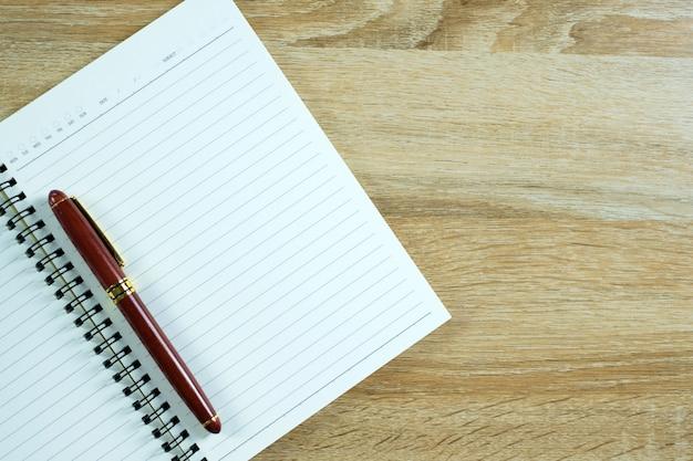 Vulpen of inkt pen met notebookpapier op tafel