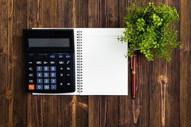 Vulpen of inktpen met notitieboekjedocument en calculator op hout