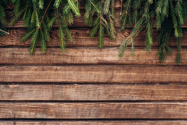 Vuren tak over een bruin houten hek. spar brunches bij het bovenstaande. winterconcept. stock foto
