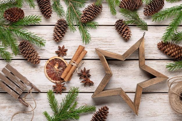 Vuren takken en kegels op lichte houten tafel, accessoires voor wintervakantie. kerstkaart, gefeliciteerd.