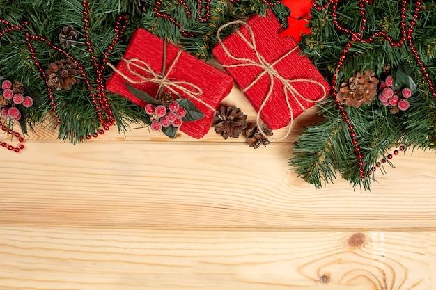 Vuren takken met kerst ornamenten en cadeau op houten