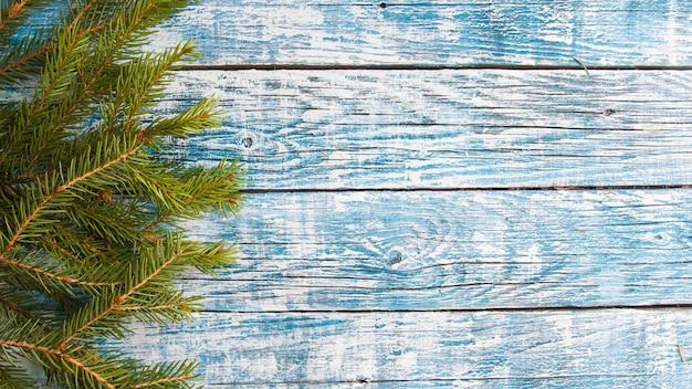 Vuren takken op een blauwe houten achtergrond, kopie ruimte bovenaanzicht
