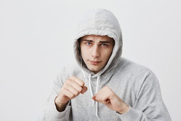 Vurige en zelfverzekerde jonge donkerharige man in sportkleding met vuisten voor zich alsof hij klaar is om te vechten of een uitdaging aan te gaan, lippen achtervolgend, met een vastberaden uitdrukking op zijn gezicht.