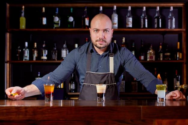 Vurige show aan de bar. de barman maakt een hete alcoholische cocktail en ontsteekt een reep. barman bereidt een vurige cocktail. vuur op bar.