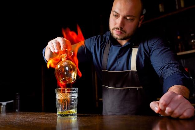 Vurige show aan de bar. de barman maakt een hete alcoholische cocktail en steekt de bar aan. barman bereidt een vurige cocktail. vuur op bar.