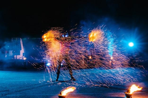 Vuurshow, dansen met vlammen, mannelijke meester jongleren met vuurwerk, optreden buitenshuis, tekent een vurig figuur in het donker, heldere vonken in de nacht. een man in een pak led danst met vuur.