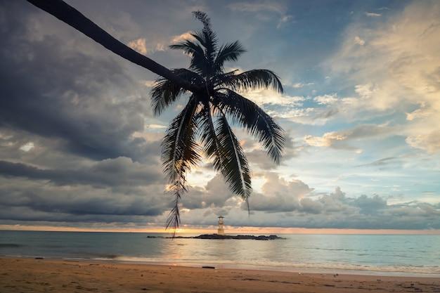 Vuurtoren baken toren en kokosnoot boom op nang thong strand bij zonsondergang in khao lak in phang nga, thailand. zeegezicht op beroemde reisbestemming.