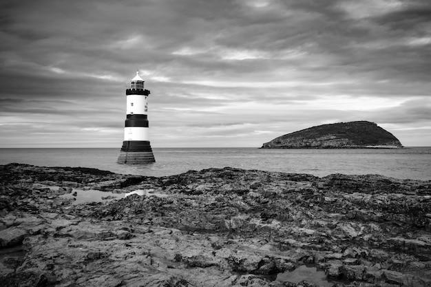 Vuurtoren dichtbij puffin-eiland in zwart-wit