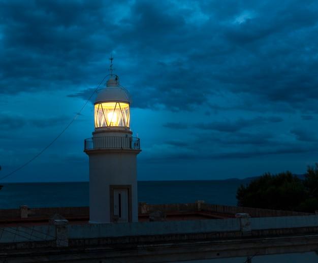 Vuurtoren die bij donkere nacht op kust spanje gloeit