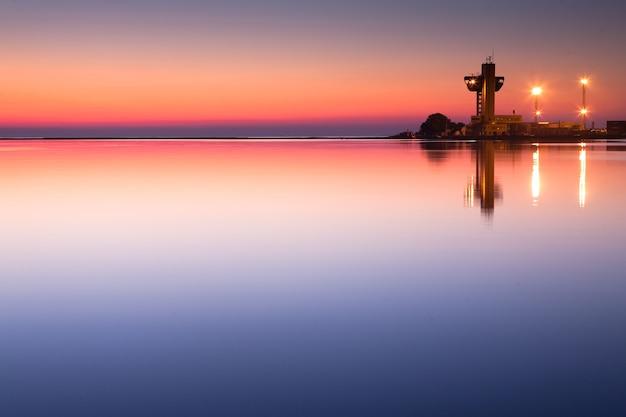 Vuurtoren en havenlichten op de achtergrond van de kalme zee vóór zonsopgang