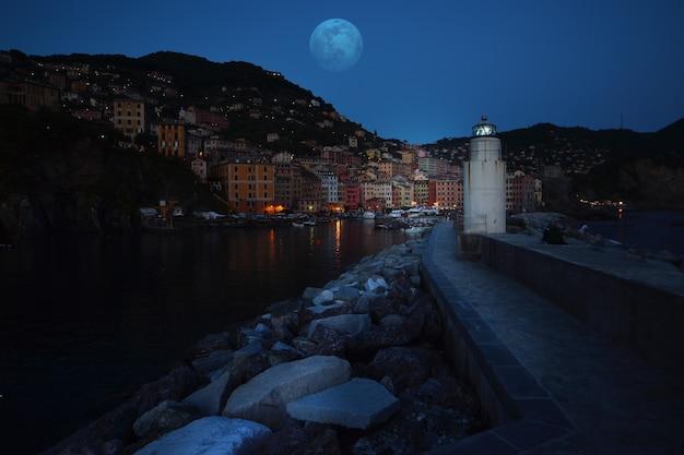 Vuurtoren 's nachts met geweldige volle maan boven de zee