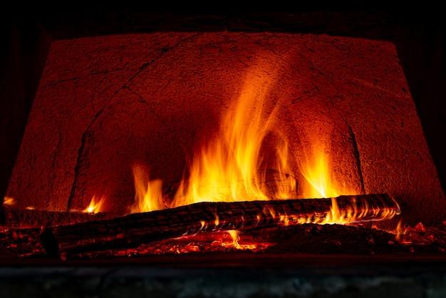 Vuurvaste bakstenen pizzaoven die bestand is tegen hoge temperaturen met brandhout dat wordt verbrand en voorbereid voor het bakken van pizza's.