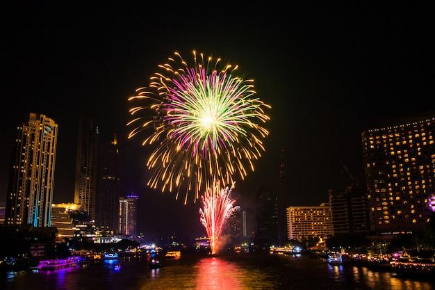 Vuurwerk kleurrijk op de meningsachtergrond van de nachtstad voor vieringsfestival.