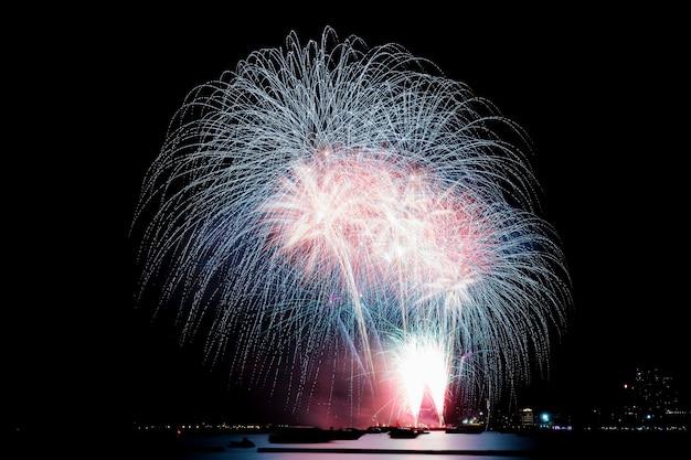 Vuurwerk op strand bij hemel aan nacht.