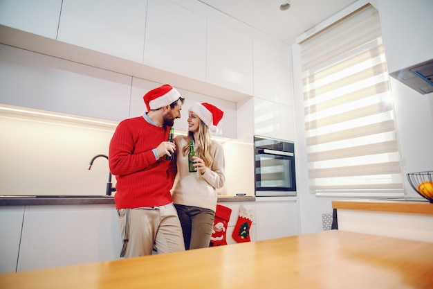 Waanzinnig verliefd stel met kerstmutsen op hoofden die op het aanrecht leunen, bier vasthouden en flirten. kersttijd