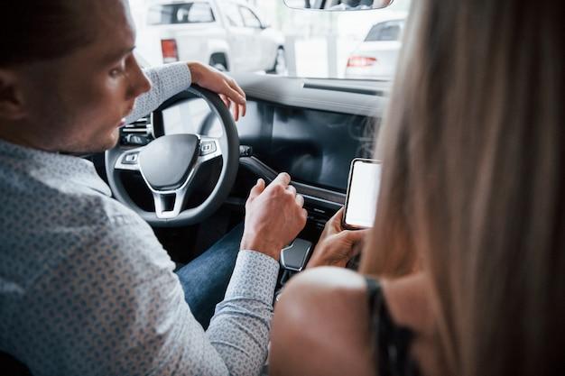 Waar gaan we heen? positieve manager die kenmerken van de nieuwe auto toont aan vrouwelijke klant