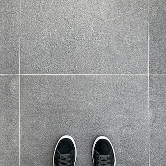 Waar ik sta, zwarte sneakers op grijze ruwe oppervlaktetegels.