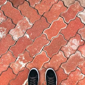 Waar ik sta, zwarte sneakers op rode bakstenen tegels.