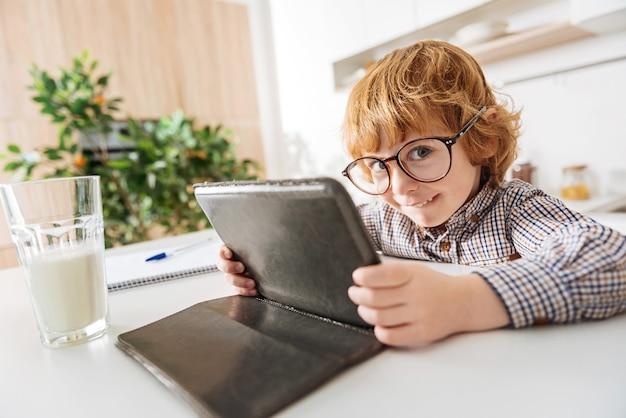Waar kijk je naar. goofy schattige roodharige jongen zit 's ochtends aan de tafel terwijl hij een bril draagt en iets leest op zijn gadget