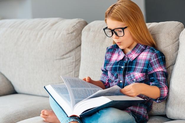 Waar was dat hoofdstuk? mooi klein meisje met een bril die een boek leest terwijl ze thuis op de bank in lotuspositie zit