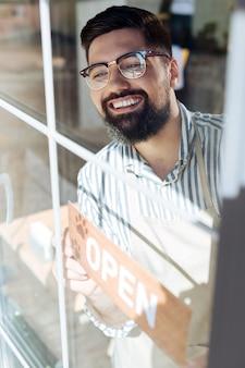 Waar zijn bezoekers. positieve gelukkige man die naar het raam kijkt terwijl hij op zijn bezoekers wacht