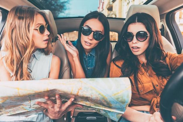 Waar zijn we? drie mooie jonge vrolijke vrouwen die verward kijken en stadsplattegrond vasthouden