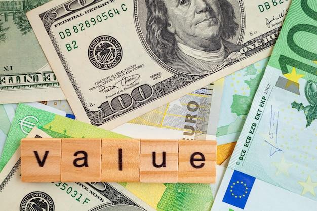 Waarde-inscriptie op houten kubussen op de textuur van amerikaanse dollars en eurobankbiljetten