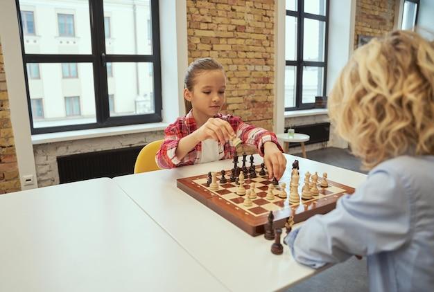 Waardige tegenstander, mooi klein meisje dat schaak speelt met haar vriend terwijl ze aan tafel zit in