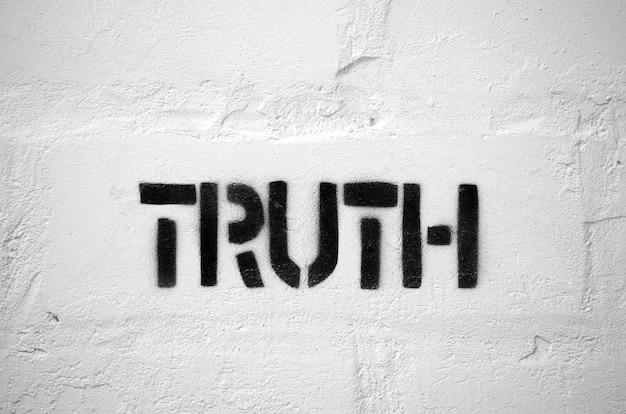 Waarheidswoord stencilafdruk op de witte bakstenen muur