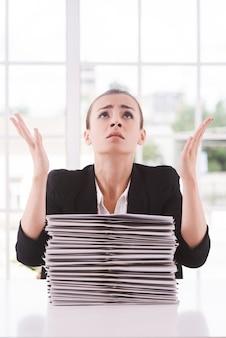 Waarom ik? depressieve jonge vrouw in pak die opkijkt en gebaren maakt terwijl ze aan tafel zit met een stapel documenten erop