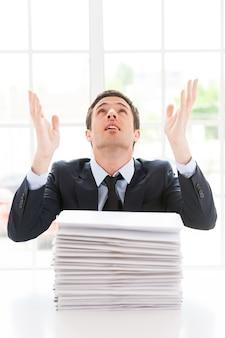 Waarom ik? depressieve jongeman in overhemd en stropdas die opkijkt en gebaren maakt terwijl hij aan de tafel zit met een stapel documenten erop