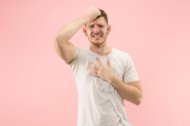 Waarom is dat. mooie mannelijke halve lengte portret geïsoleerd op trendy roze studio achtergrondgeluid. jonge emotioneel verraste, gefrustreerde en verbijsterde man. menselijke emoties, gezichtsuitdrukking concept.