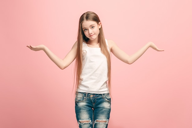 Waarom is dat. mooie vrouwelijke halve lengte portret op trendy roze studio achtergrondgeluid. jong emotioneel verrast, gefrustreerd en verbijsterd tienermeisje