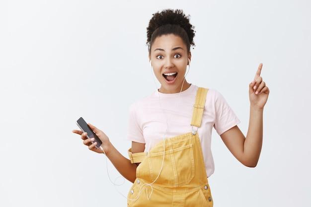 Waarom staan, laten we dansen. goed uitziende vrouwelijke trendy vrouw met donkere huid en krullend haar in stijlvolle gele overall, beweegt op het ritme van muziek, houdt smartphone vast en luistert liedjes in oortelefoons