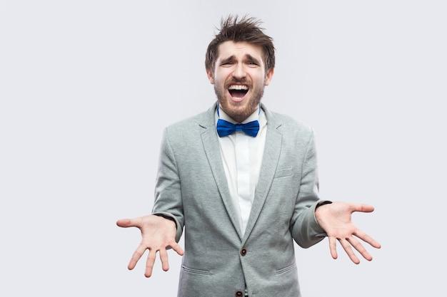 Waarom? wat? portret van een verwarde knappe bebaarde man in een casual grijs pak, blauwe vlinderdas die staat en naar de camera kijkt met opgeheven armen en vraagt. indoor studio-opname, geïsoleerd op lichtgrijze achtergrond