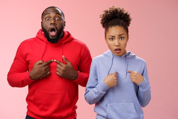 Waarom wij. geschokt gestoord klagen twee afro-amerikaanse broer zus wijzende borst wijsvingers fronsen gehinderd overstuur man ogen verwijden verrast vrouw fronsen verdriet, staande roze muur