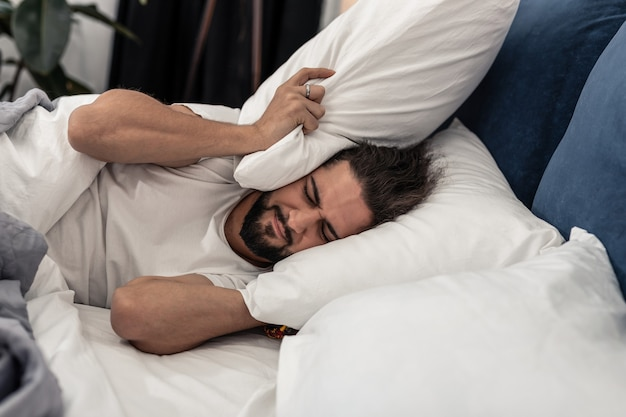 Waarom zo vroeg. ongelukkige trieste man die in bed wil blijven terwijl hij het geluid van de wekker hoort