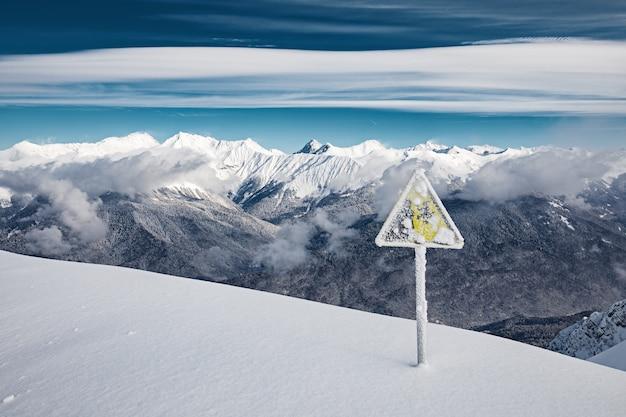 Waarschuwingsbord bedekt met sneeuw aan de rand van de skipiste in de bergen