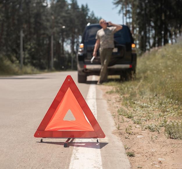 Waarschuwingsbord met rode driehoek op de weg na autopech en wazige bestuurder die op mobieltje spreekt...